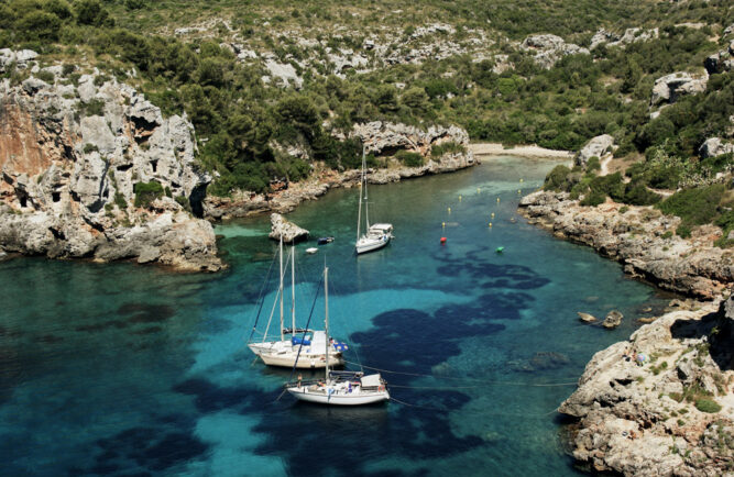 Weiße Segelboote auf seichtem, türkisem Wasser in einer Bucht. Felsige Wände und Wälder auf dem Festland