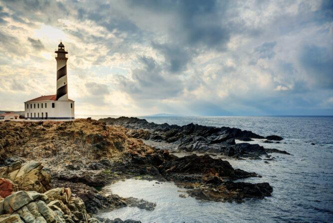 Ein rot und weiß gestreifter Leuchtturm steht auf einem Felsen in einer Bucht. Der Fels ist dunkel, am Himmel sind viele Wolken