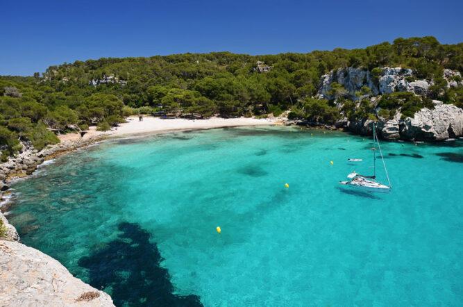 Eine Bucht mit einem weißen Sandstrand, hell türkisem Wasser. Ein Segelboot liegt in der Bucht. Hinter dem Strand sind grüne Wälder