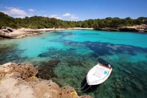 Türkisblaue Bucht, niedriges Wasser sodass man Algen erkennen kann, ein weißes Boot liegt im Vordergrund vor Anker, im Hintergrund ein Strand mit Wald dahinter