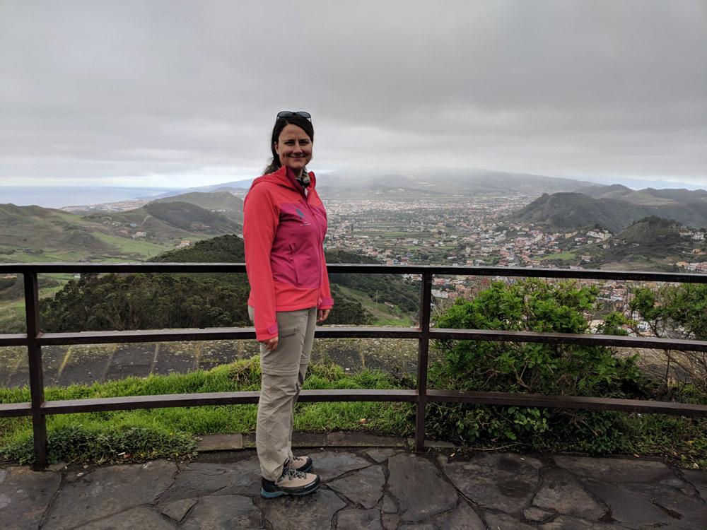portraitfoto von frau in pinker jacke, hügelige landschaft im hintergrund