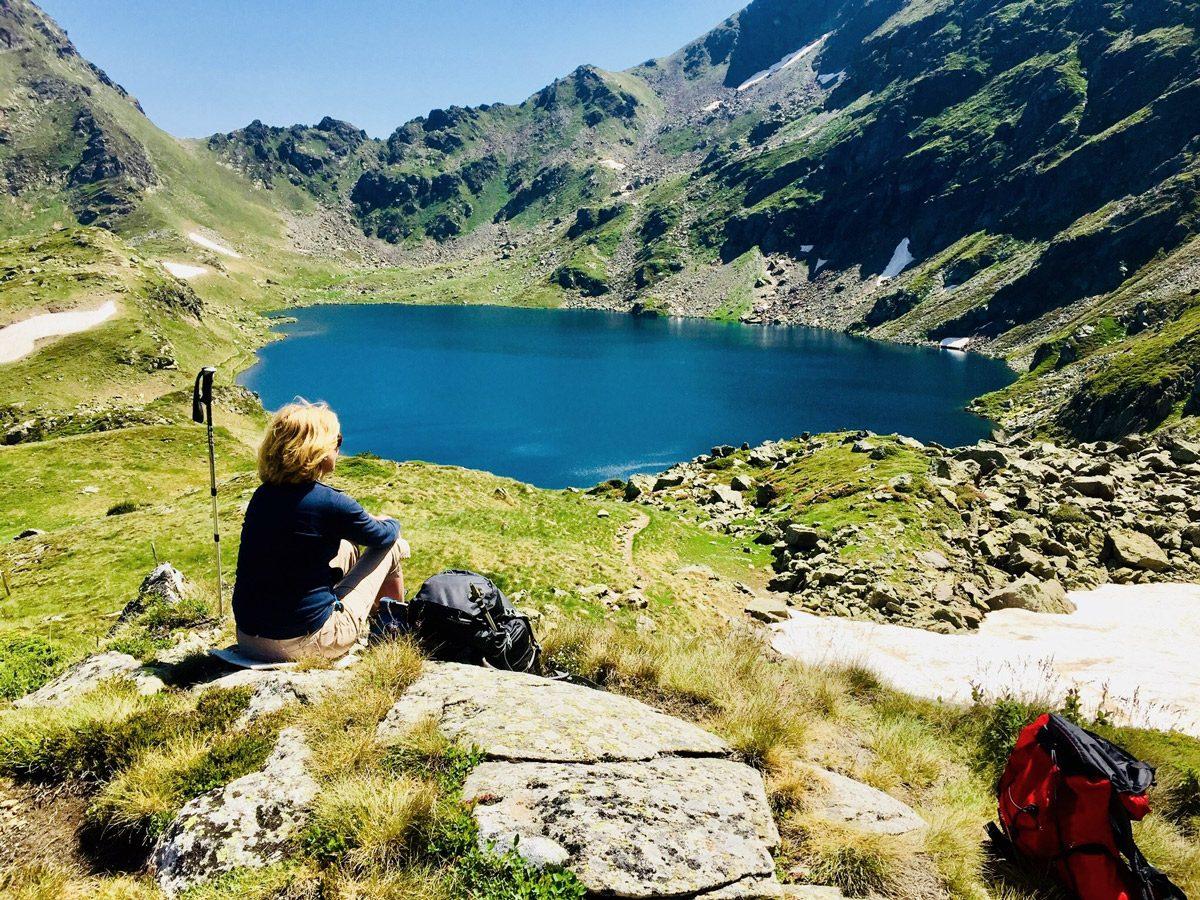 blauer Bergsee mit Wandererin im Vordergrund