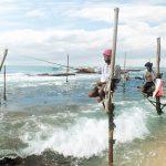 Mehrere Männer auf dünnen Stöcken die im Meer stehen, Angelruten in der Hand