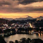 Beleuchtete Häuser und Straßen einer Stadt um einen See
