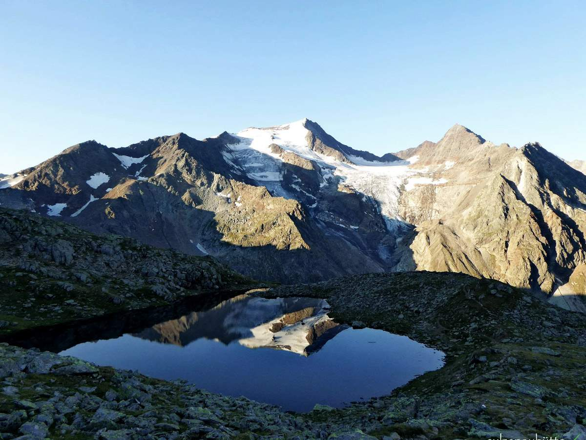 Ausblick auf Gletscher und Berge hinter Gebirgssee