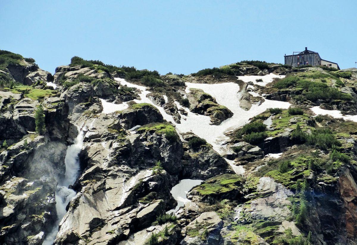 über dem Almboden drohnt die Hütte oben an der Kante