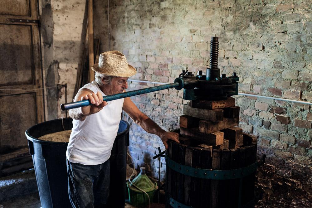 Bauer dreht an Maschine / Weinpresse