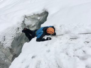 Mann mit blauer alpinen Ausrüstung wird an Seil aus Gletscherspalte gezogen.