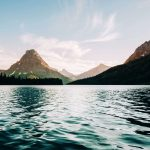 Tiefes, hellblaues Wasser mit gigantischer Aussicht auf Berge, Glacier Nationalpark. © Tevin Trinh