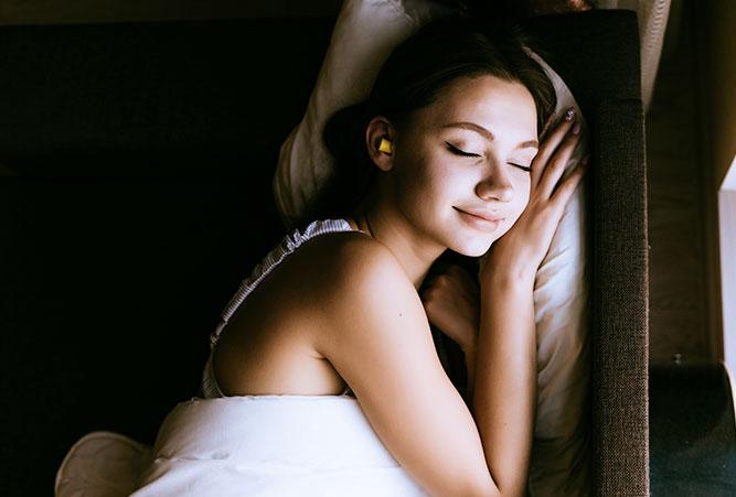 tipps-huettenuebernachtung-schlafende-frau-mit-ohrstoepsel