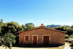 Steinerne Hütte umgeben von grünen Bäumen, blauer Himmel