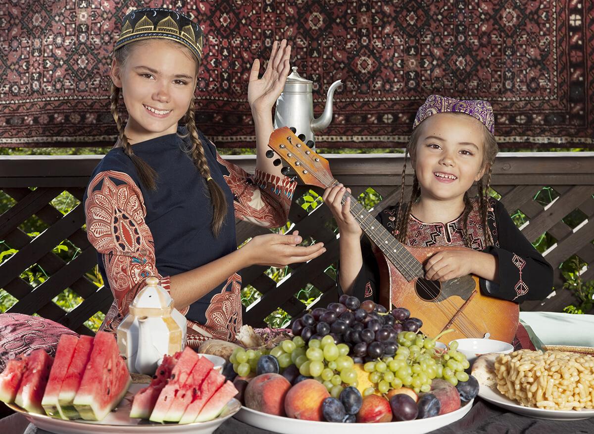 Usbekische Mädchen in traditioneller Kleidung am gedeckten Tisch