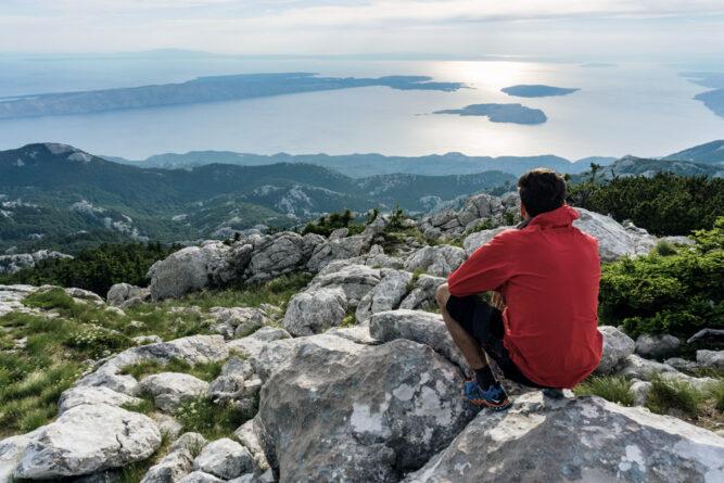 Mann mit roter Jacke sitzt auf Felsen über einer Küste