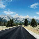 Einsame Straße, die schneebedeckten Berge des Grand Teton Nationalparks im Hintergrund. © Victoria Dihua