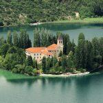 Kloster auf einer Insel in einem smaragdgrünen See