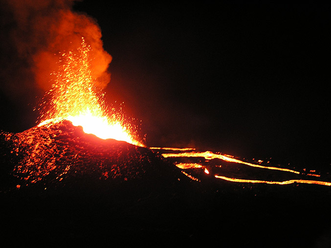 feuerspeiender vulkan in der nacht