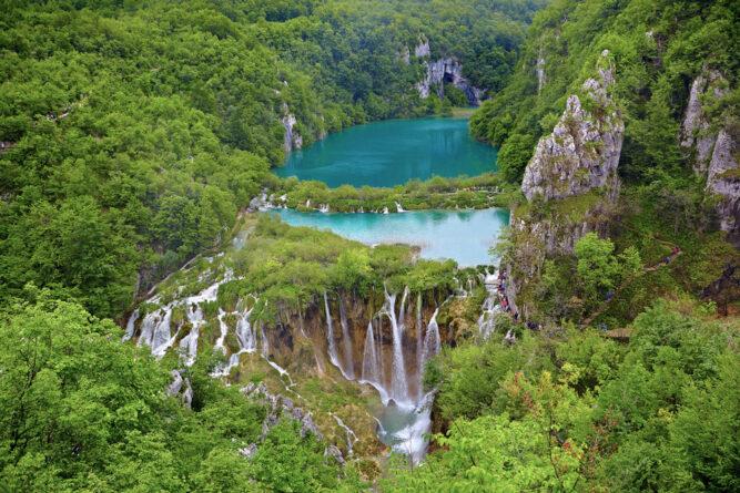 Türkises Wasser und kleine Wasserfälle in grünem Wald