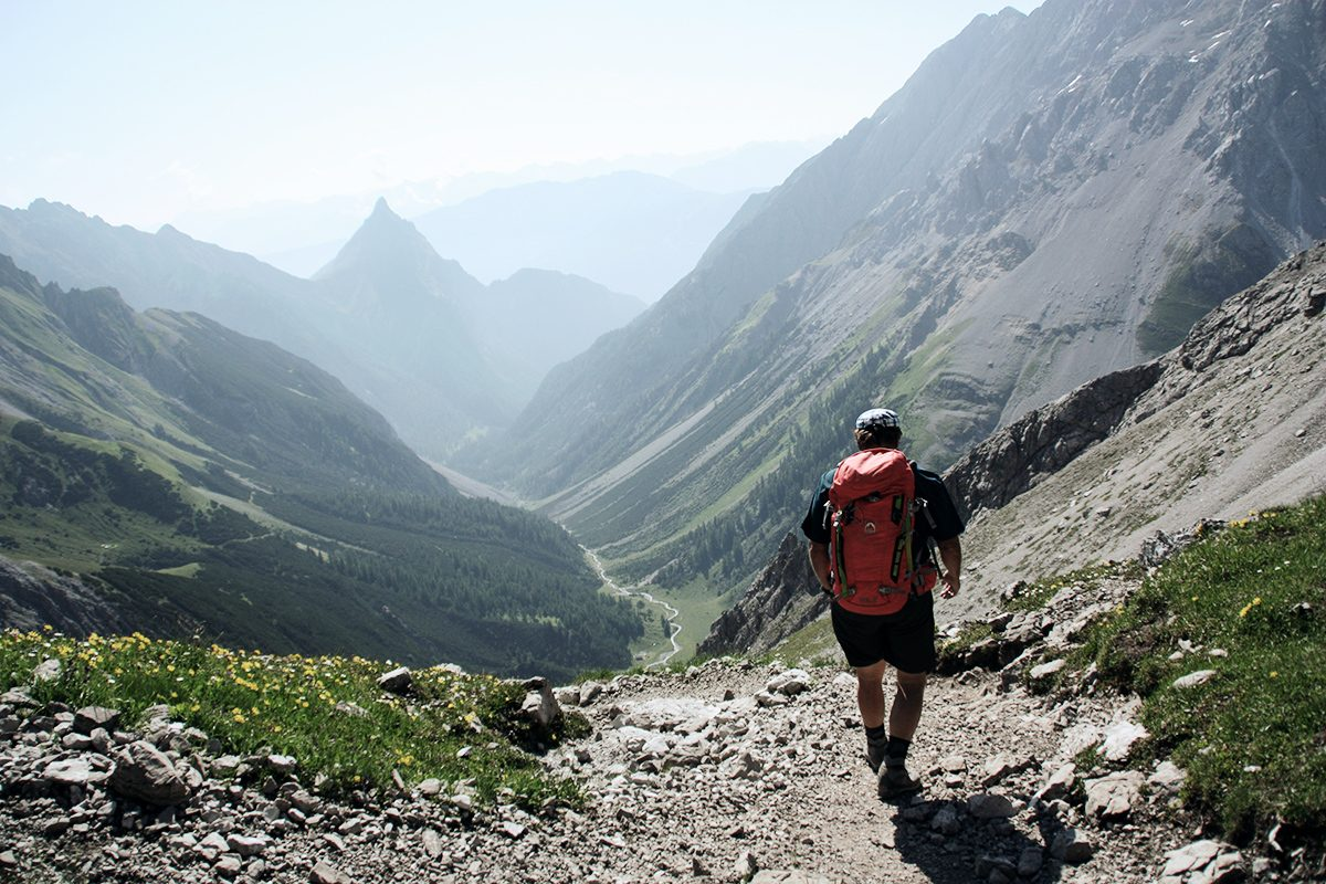 Junger Mann schreitet bei Sonnenschein in ein Tal. Panoramablick in den grünen und teilweise felsigen Talkessel.