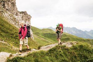 Zwei junge Frauen wandern entlang einem schmalen Wanderweg inmitten grüner Berglandschaft